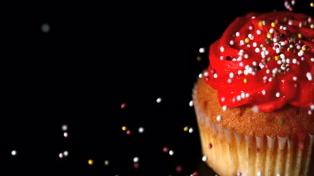 borrifar : Sprinkles falling onto a cupcake in slow motion