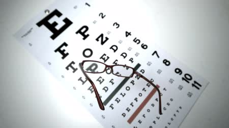 optyk : Black reading glasses falling onto eye test in slow motion Wideo