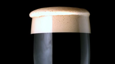 İrlanda :  Foam head settling on pint of beer on black background in slow motion