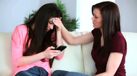 крик : Woman receiving bad news on her phone and her friend is comforting her in the living room