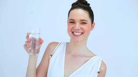içme : Smiling woman drinking a glass of water on white background Stok Video