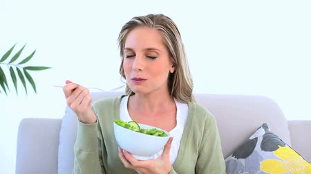 jeść : Woman eating a healthy salad on her couch