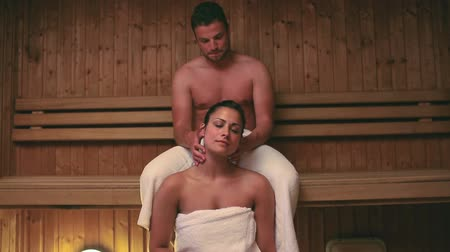 dokunaklı : Man giving his girlfriend a neck massage in the sauna at the hotel spa