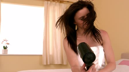 toalhas : Young woman sitting on her bed drying her hair in slow motion