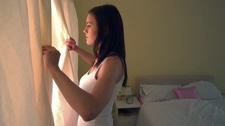 perdeler : Young woman opening bedroom curtains in the morning in slow motion Stok Video