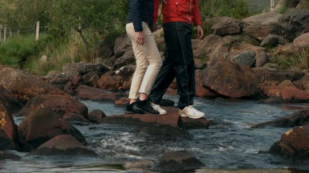 hiking : Couple crossing a stream together in the countryside in slow motion