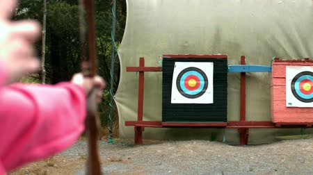 цель : Woman shooting bow and arrow to the target in slow motion