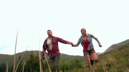fit : Happy couple running hand in hand though the countryside in slow motion Stock Footage