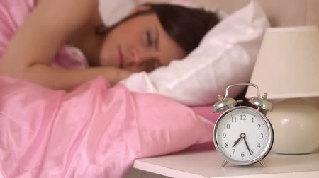 uykuda : Alarm clock ringing and waking a sleeping woman in a bedroom in slow motion Stok Video