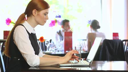 redhead suit : Serious businesswoman working on her laptop in a classy restaurant