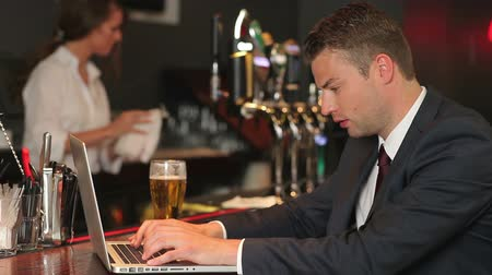 krawat : Serious businessman working on his laptop while drinking beer in a pub