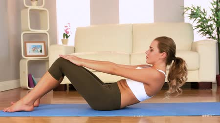 atletismo : Toned brunette doing sit ups at home in bright living room Stock Footage