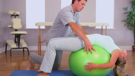 terapia : Physiotherapist working with a patient on an exercise ball to stretch her back in his office
