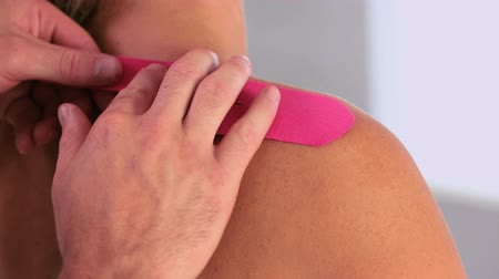 fizjoterapeuta : Physiotherapist applying pink kinesio tape to patients back in his office Wideo