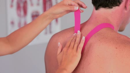 fizjoterapeuta : Physiotherapist applying pink kinesio tape to male patients back in her office Wideo
