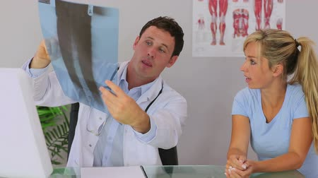 fizjoterapeuta : Chiropractor discussing with his patient and showing her an xray
