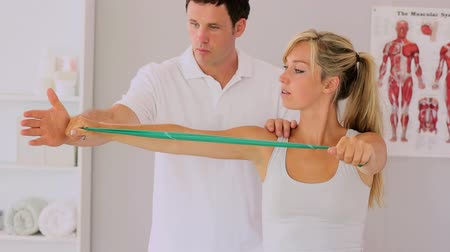 fizjoterapeuta : Physiotherapist using a resitance band with his patient and talking in his office Wideo