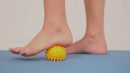 masaż : Girl using yellow massage ball on her foot on blue mat Wideo