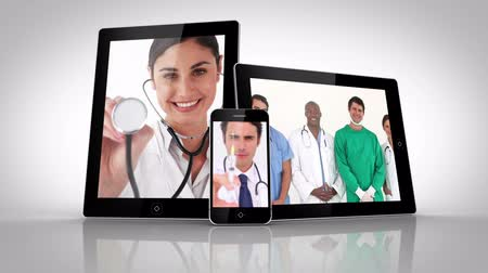 etkileşim : Electrical devices showing different doctors on white background Stok Video