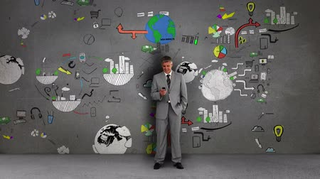 marketing : Businessman standing in front of animated business flowcharts on grey wall