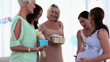 daireler : Friends having a baby shower party at home in living room Stok Video
