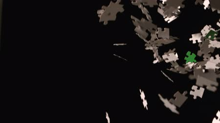 кусок : Jigsaw pieces falling on black background in slow motion