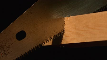 wood : Saw cutting through wood on black background in slow motion Stock Footage