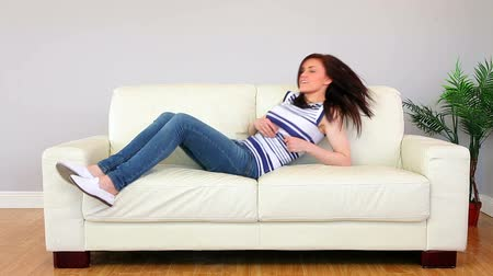 calçados : Pretty brunette flopping down on the couch in living room at home