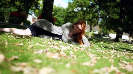 vöröshajú : Calm redhead posing lying on green lawn wearing a summerdress Stock mozgókép