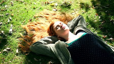 vöröshajú : Young redhead relaxing on lawn in bright sunshine