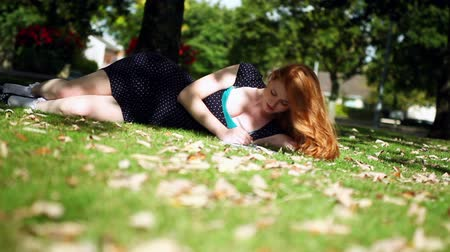vöröshajú : Cute young redhead doing assignments lying on green lawn Stock mozgókép