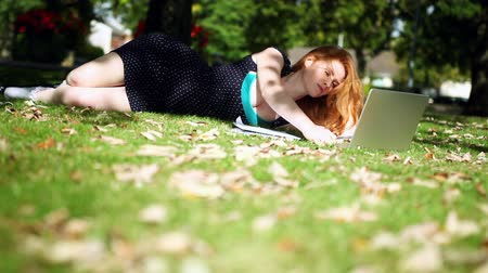 vöröshajú : Lovely redhead using her notebook for doing assignments lying on green lawn