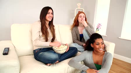 assistindo : Pretty young friends eating popcorn while watching television in bright living room