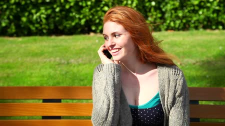 ruivo : Cute woman sitting on bench while phoning with her smartphone