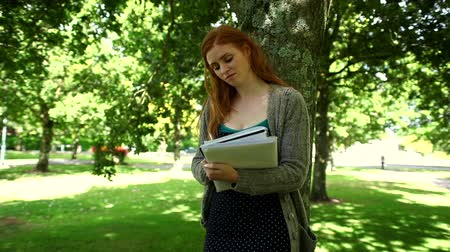vöröshajú : Lovely thinking redhead doing assignments standing in park on sunny day