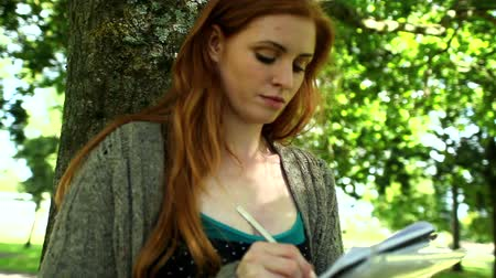 vöröshajú : Concentrated redhead doing assignments sitting on lawn leaning against tree