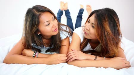 fekvő : Pretty happy sisters lying on bed chatting in bright bedroom
