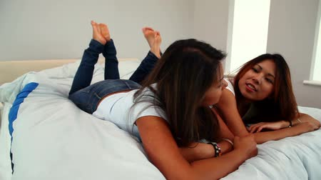 сестра : Attractive sisters lying on bed chatting in bright bedroom Стоковые видеозаписи