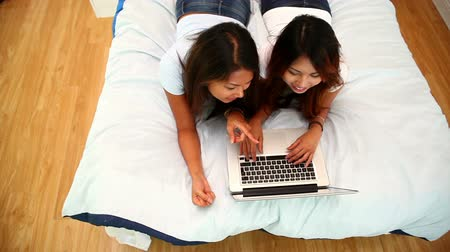 o : Attractive sisters lying on bed using laptop in bright bedroom