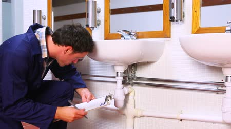 plumber : Handsome plumber looking at sink holding clipboard in a public bathroom Stock Footage