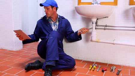 szerelő : Handsome plumber fixing sink and checking tablet pc in a public bathroom Stock mozgókép