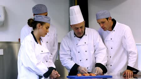 chef : Head chef showing his trainees how to fillet a salmon in a commercial kitchen