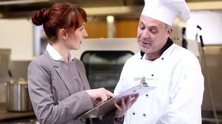 yönetici : Restaurant manager speaking with head chef in a commercial kitchen