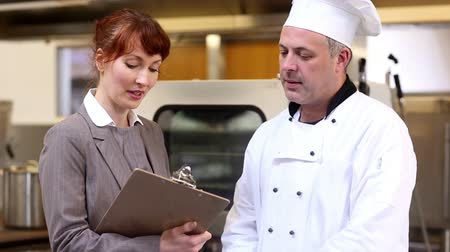 vágólapra : Restaurant manager chatting with head chef in a commercial kitchen Stock mozgókép