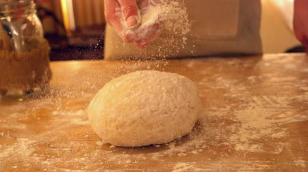 мучной : Female hand sprinkling flour on ball of dough on a floury surface in slow motion Стоковые видеозаписи