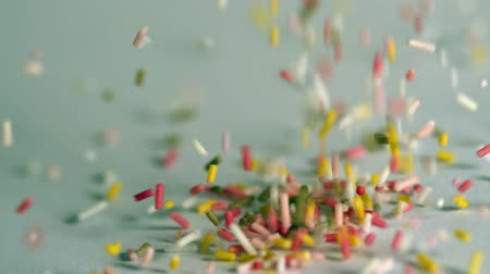 borrifar : Sprinkles pouring onto blue surface in slow motion Stock Footage