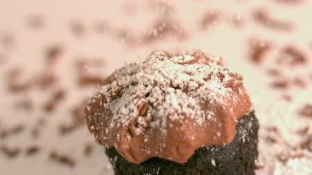 jegesedés : Icing sugar being sieved on chocolate frosted cupcake in slow motion