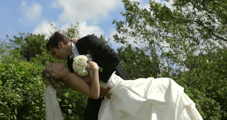 nevěsta : Groom kissing his pretty new wife outside on their wedding day