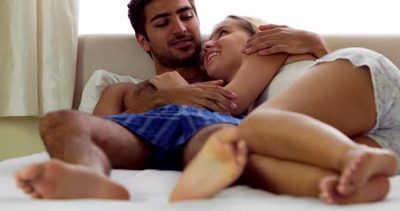 любовь : Cute couple speaking and cuddling in bed at home in bedroom