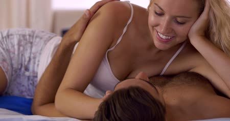 любовь : Young couple kissing and cuddling in bed at home in bedroom